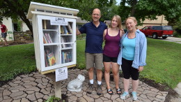"Craig, Anna and Elianor beside their new neighborhood ""little free library."""
