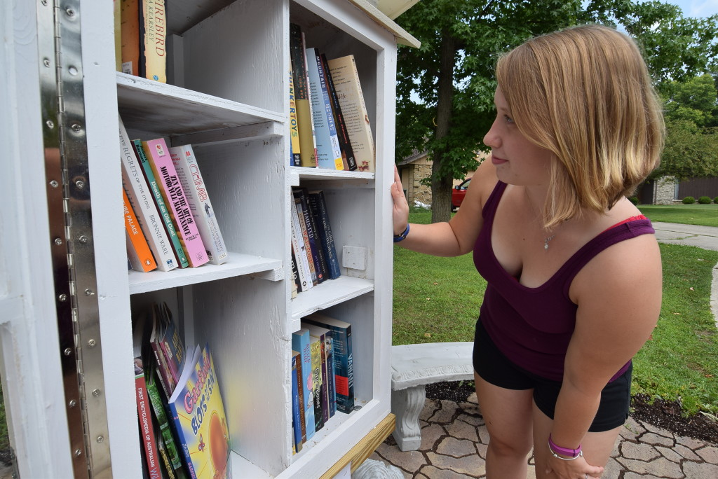 Elianor Priebe takes a look at some of the books in the little free library in Johnson Woods addition. Photo: Mike Rhodes