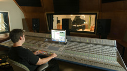 An audio engineer operating a digital audio mixing board is shown in this provided photo.
