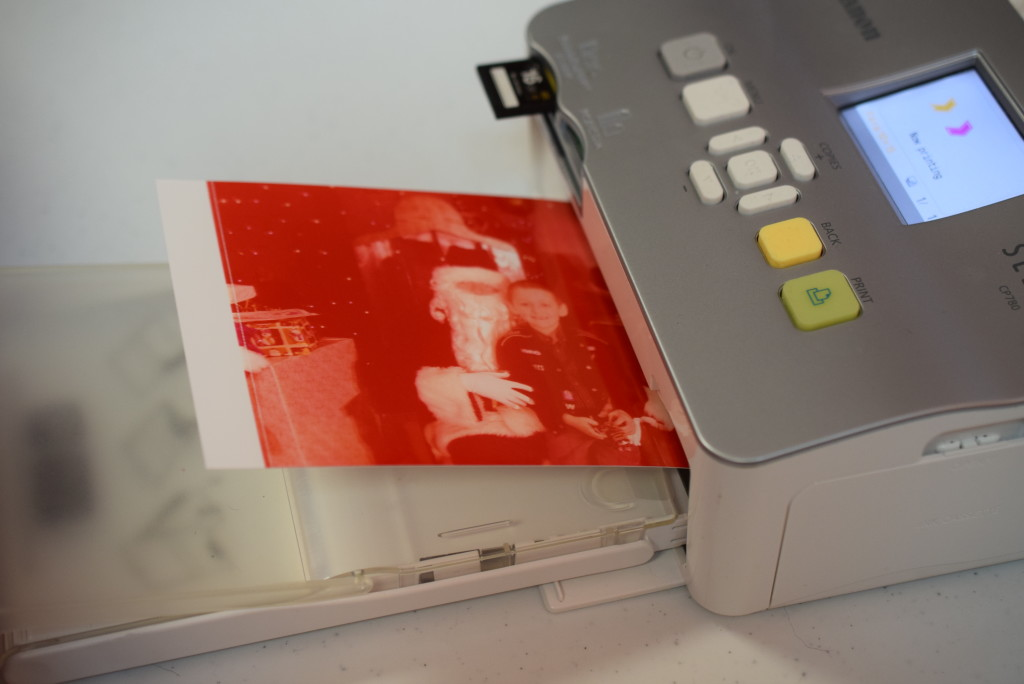 One of Santa's digital pictures gets printed out. The printer makes a few passes to achieve full color, before it is handed out to a child.
