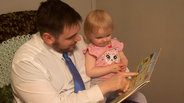 "Nate Rose and his daughter Noelle reading the first Imagination Library book, ""The Little Engine That Could."" Photo provided."