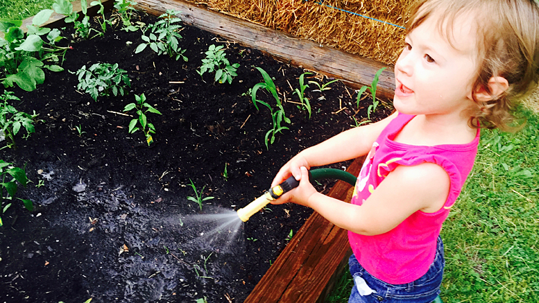 Learning to water the garden. Photo by: Matt Howell