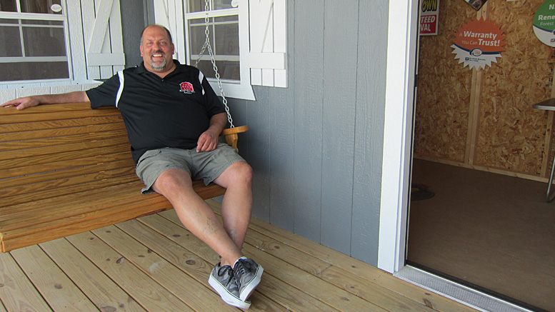 Scott Quirk, owner of The Barn Lot, relaxes on the porch swing of a tiny house. Photo by: John Carlson