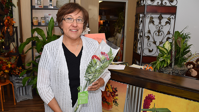 Sharon Grubbs with a Petal it Forward bouquet. 650 bouquet's will be given away on Wednesday. Photo by: Mike Rhodes