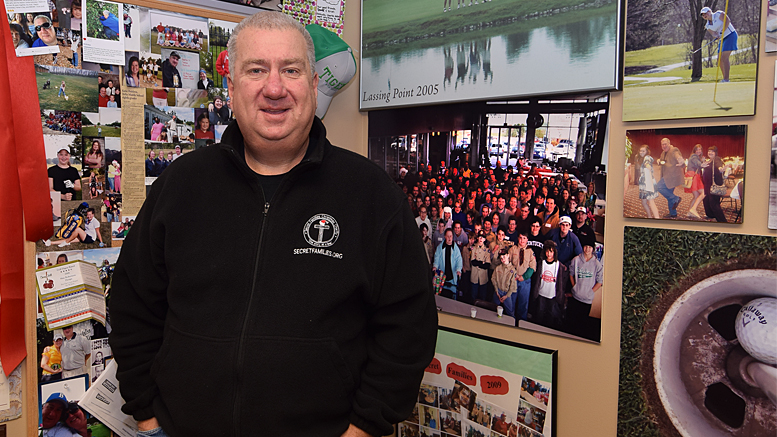 "Al Holdren is pictured in his office standing beside hundreds of photos of thousands of volunteers who participate in ""Secret Families."" Photo by: Mike Rhodes"