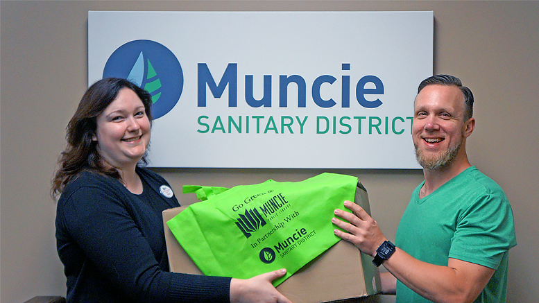 MPL employee Sara McKinley and MSD employee Jason Donati look at reusable tote bags made possible by a partnership between Muncie Public Library and Muncie Sanitary District. Photo by: Loren McClain, Muncie Public Library