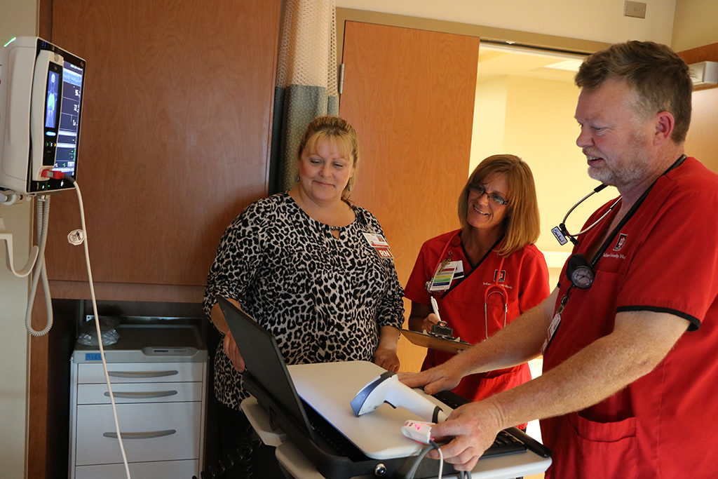 resa Elliott, Clinical Operations Manager at IU Health Ball Memorial Hospital works alongside nurses on 9N as they look into a patient's care.
