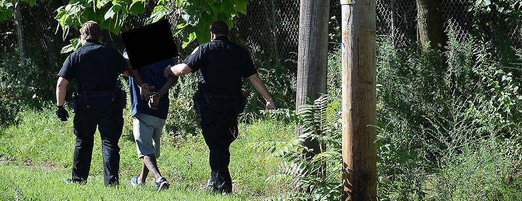 An alleged hit and run suspect is apprehended moments after fleeing the scene of a car accident. Photo by: Mike Rhodes
