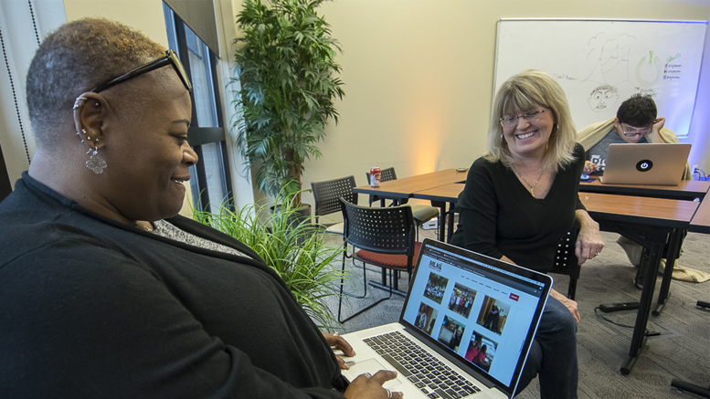 Watasha Griffin (L) is pictured reviewing the new Martin Luther Dream Team website, while Susan Fisher (R) looks on during the 2018 Website Thru The Night event. Photo by: Mike Rhodes.