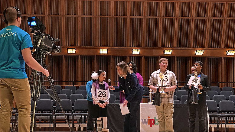2018 WIPB-TV Spelling Bee Champion is interviewed by host Michelle Kinsey during the awards ceremony. Andrew Toney and Samori McKell-Jeffers stand by, holding their first runner-up and second runner-up trophies, respectively. Photo provided.
