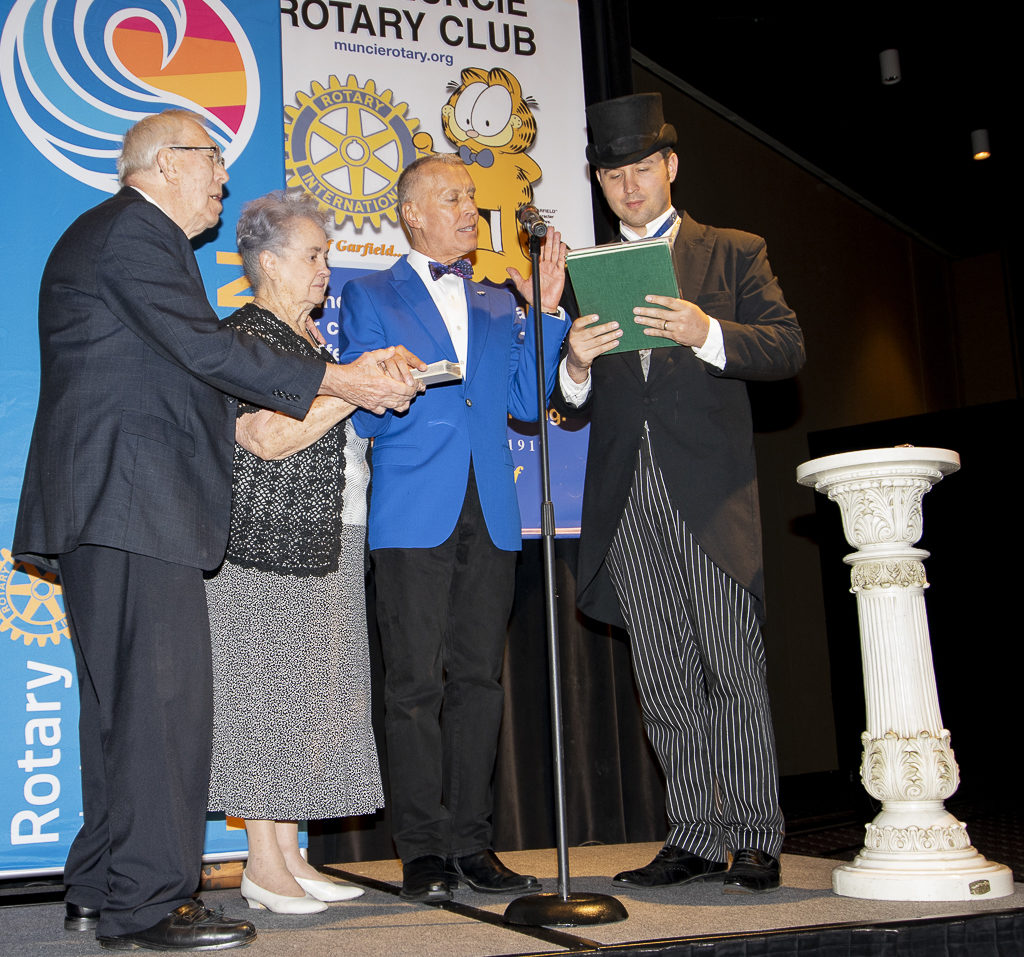 Dale Basham takes the Oath of Office with his parents by his side (L) and Jonathan Kipp Becker (R) who portrayed Paul Harris, Founder of Rotary during the evening.
