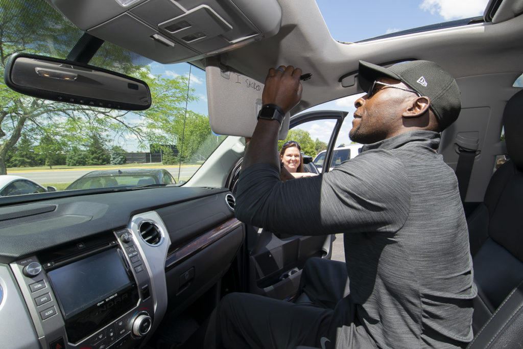 Kyla Bartle looks through the window as Robert Mathis signs the visor of the new Toyota Tundra truck her family purchased. Photo by: Mike Rhodes