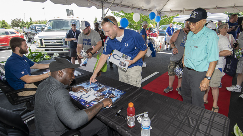 Jack Doyle and Robert Mathis sign autographs and give posters to fans at the Toyota and Kia of Muncie Tent Sale. Photo by: Mike Rhodes