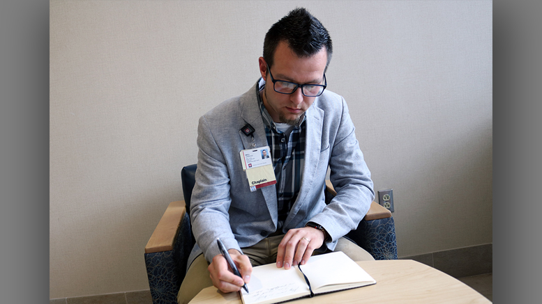 Rev. Will Grinstead, staff chaplain at IU Health Ball Memorial Hospital, takes time to make an entry in his journal. Photo by: Courtney Thomas for IU Health Ball Memorial Hospital.