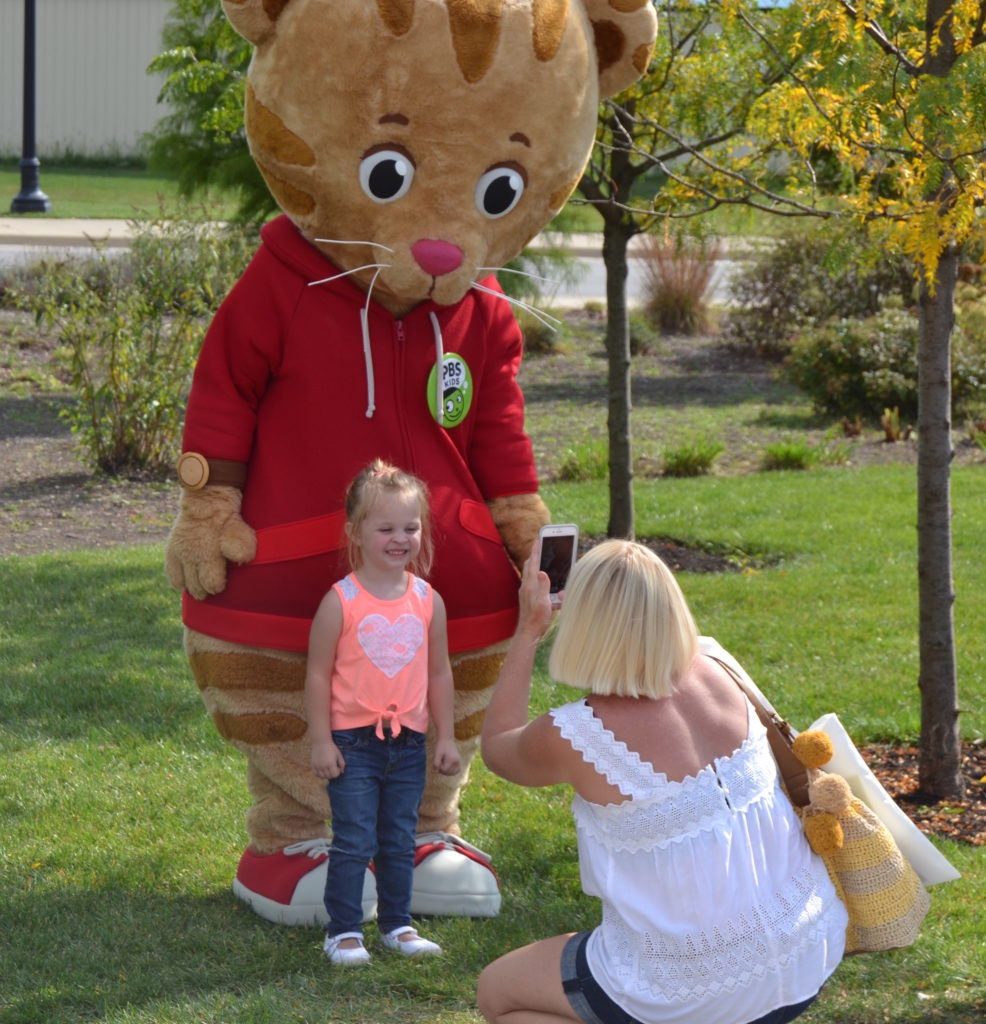 Daniel Tiger poses for a photo with a new friend at Be My Neighbor Day 2017. Photo provided.