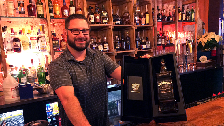 Bartender Joshua Banister shows off Frank Sinatra's Jack Daniels. Photo by: John Carlson