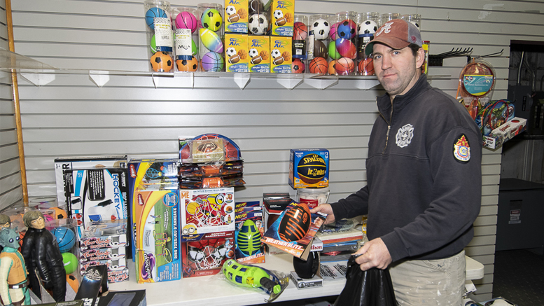 Firefighter Daniel Powell puts together a bag of new toys for a local family inside the Toys For Tots office in Southway Plaza. Photo by: Mike Rhodes