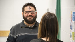 "Paul Ward is pictured talking with an associate with an Ash Wednesday ""smudge"" appearing on his forehead. Learn what that means below. Photo by: Mike Rhodes"