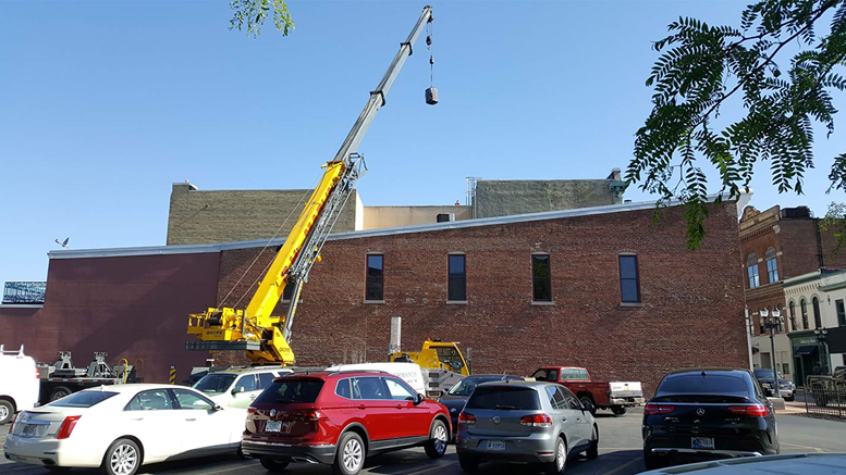 Bullock Heating & Cooling is pictured moving an HVAC unit downtown.
