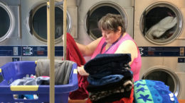 Customer Cheryl Minor folds her clothes during the LAUNDRY LOVE event. Photo by: Nancy Carlson