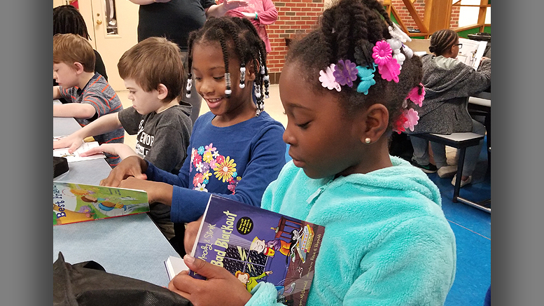 Damiyah Watkins, Tionna Canady and Jacob Johnson, South View Elementary students, could not wait to begin reading their Summer Book Give Away. Photo provided by United Way
