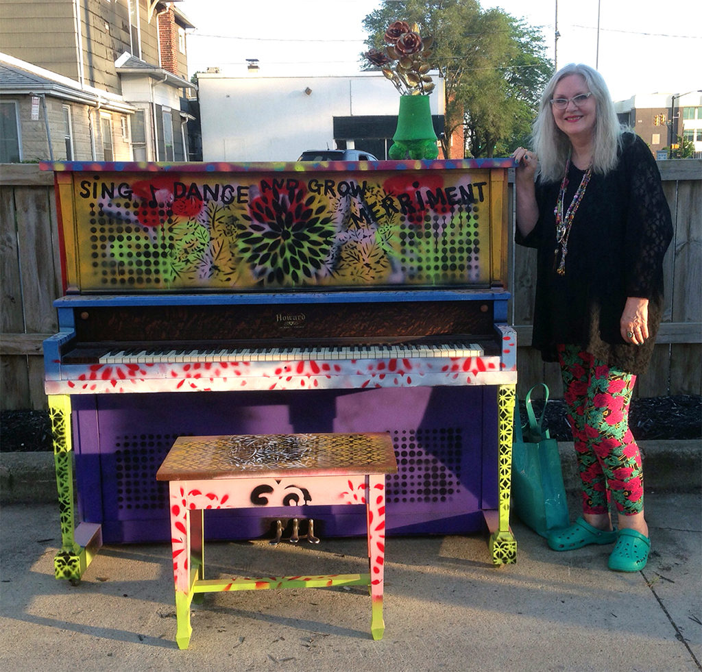 Debra Gindhart poses with her finished piano art, titled Sing, Dance and Grow Merriment, at an unveiling event on June 28, 2019 at Madjax. Photo provided