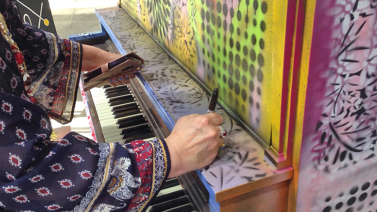 Debra Gindhart signs her piano at Madjax's Second Thursday event on July 11, 2019. Gindhart titled her work Sing, Dance and Grow Merriment. Photo provided