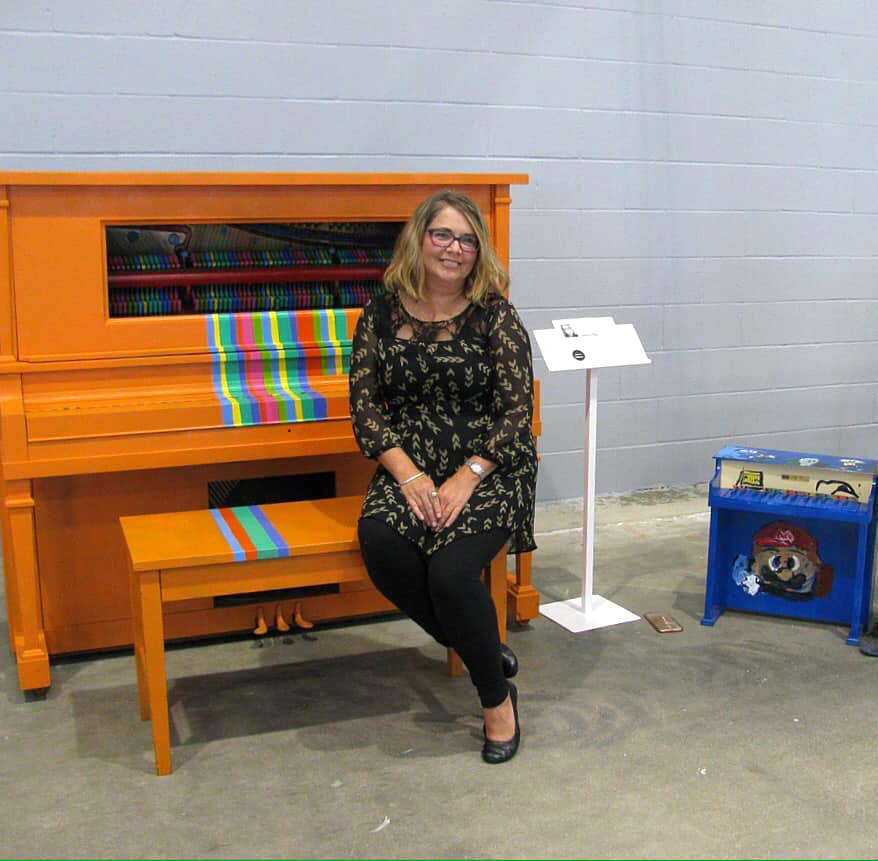 Denise King poses with her finished piano, titled Chromesthesia, at at Madjax's Second Thursday event on July 11, 2019. Photo provided