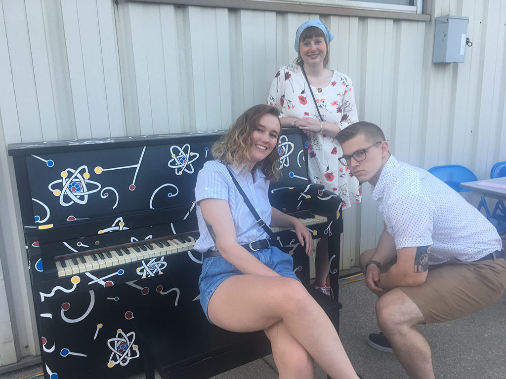 Sarah Vise, Maggie Weeks-Foy, and Quinn Hurley pose in front of the piano they painted together. The piano art was designed by Vise, a recent Ball State University graduate with degrees in physics and astronomy. Photo provided