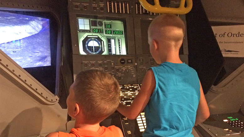 Two young museum visitors fly a lunar landing simulator. Photo by: Nancy Carlson