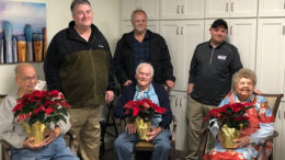 Woof Boom Radio staff members Mitch Henck, Brian Casey, and Zack Johnson are pictured with Sugar Fork Crossing nursing home residents during a Project Poinsettia delivery. Photo by: Lindsey Martin