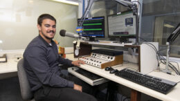 Ball State TCOM student Isaac Dirrim is pictured in the Woof Boom Radio News Center during his recent internship. Photo by: Mike Rhodes