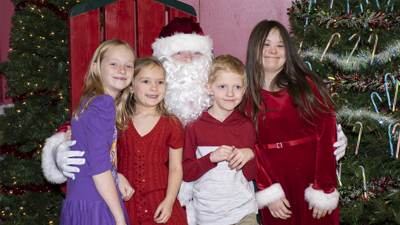 A group of kids get their picture taken with Santa at the Tiny Adams Christmas Event at Fire station #1. Photo by: Mike Rhodes