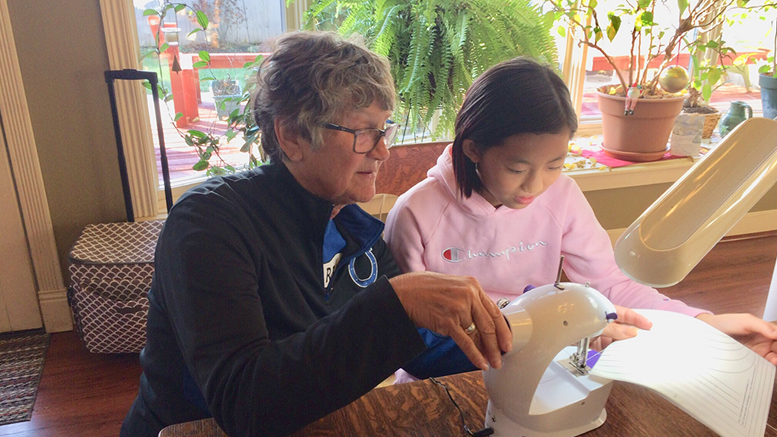 Nancy passes some sewing skills on to Jing Jing. Photo by: John Carlson