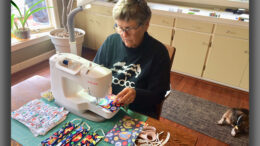 Volunteers like Nancy Carlson are among local theater seamstresses making masks. Photo by: John Carlson