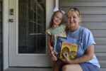 Four-year-old Isabelle Rabenstein receives books from Dolly Parton's Imagination Library, delivered by letter carrier Debbie Edwards Thompson. Isabelle is the daughter of Jordan and Zach Rabenstein. Photo provided