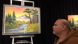 "Artist Andy Klise admires a painting displayed at ""Bob Ross Experience."" Photo by Nancy Carlson"